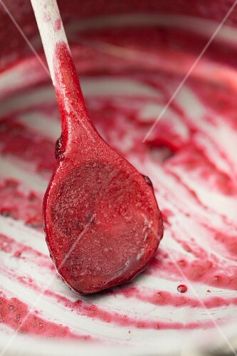 The remains of cherry jam with a wooden spoon