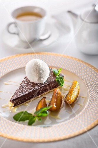 Chocolate tart with creme anglaise, pears and a scoop of milk ice cream on a festive plate