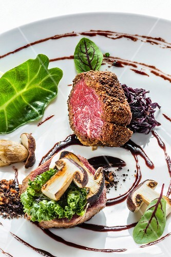A platter of game with variations of venison with porcini mushrooms, red cabbage and leafy greens