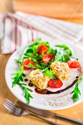 Salad with goat's cheese in an almond crust, rocket, tomatoes and balsamic sauce