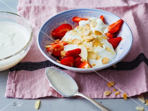Fresh strawberries with a coconut and quark topping and roasted, flaked almonds