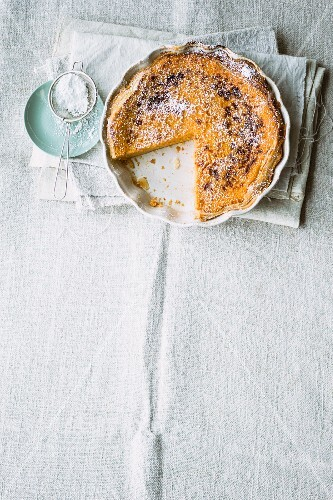 Pumpkin and apple tart with icing sugar, sliced