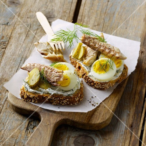 Slices of bread topped with mackerel, hard-boiled eggs and gherkins