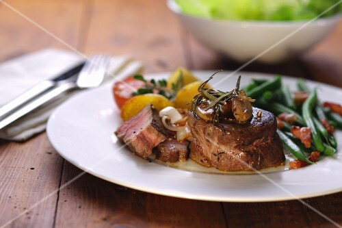 Sliced beef fillet with green beans and bacon