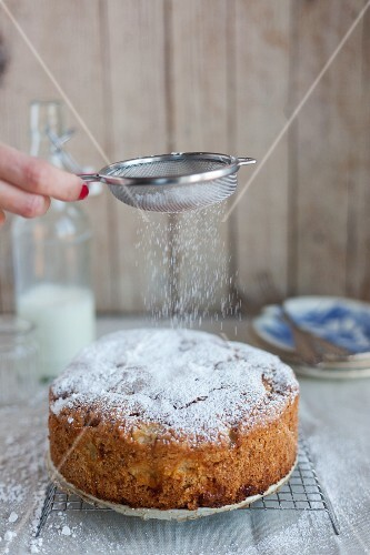 An apple and hazelnut cake being dusted with icing sugar