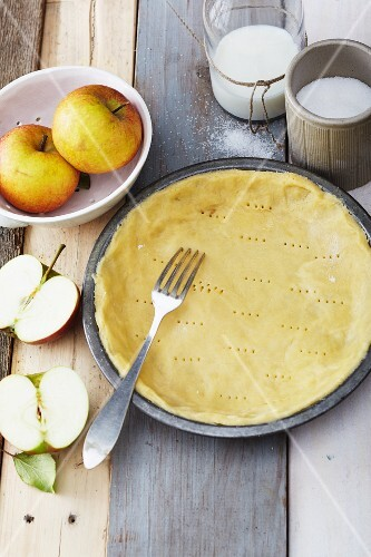 Shortcrust pastry in a baking tin being pierced with a fork ready for blind baking