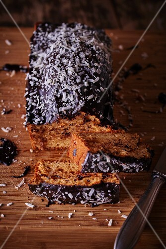 A loaf cake with chocolate glaze and grated coconut