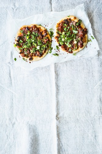 Mini Turkish pizzas topped with aubergines, mint and spring onions