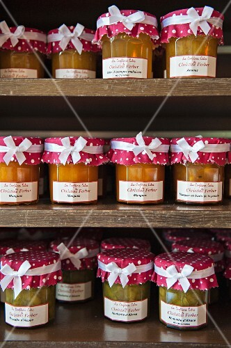 Various jams in preserving jars on a shelf in a shop