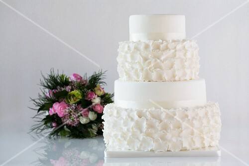 A white, four-tier wedding cake and a bridal bouquet