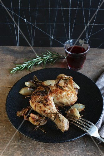 A chicken leg with onions and rosemary served with a glass of red wine
