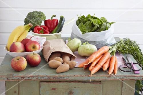 An arrangement of vegetables and fruit on a vintage kitchen cupboard