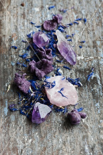 Healing stones, cornflour leaves and candied violet on a wooden surface