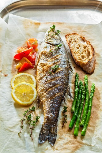 Seabass with asparagus, lemons and bread on baking paper