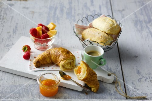 Breakfast with croissant, jam, espresso, rolls and fruit