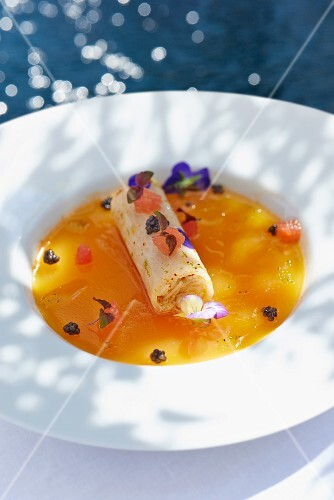 Cannelloni filled with crab in a sauce with edible flowers