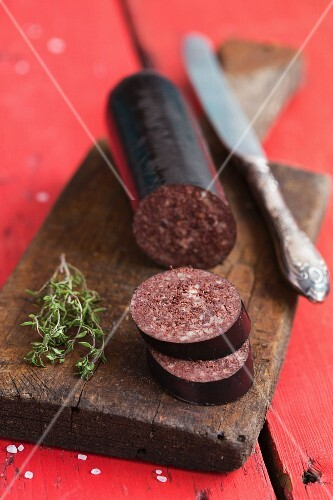 Black pudding, sliced, and fresh thyme on a chopping board