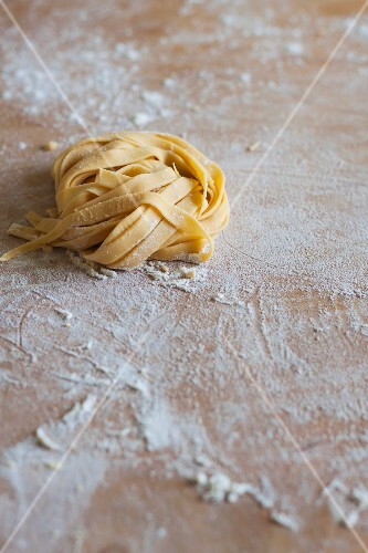 Fresh, uncooked pasta on a floured wooden board