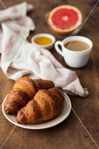 Croissants with coffee, honey and grapefruit for breakfast