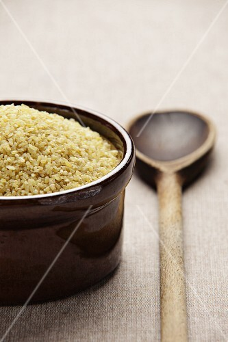 Bulgur wheat in a ceramic bowl with a wooden spoon next to it