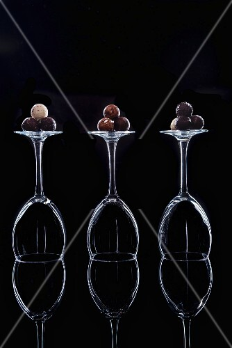 Chocolate truffles on overturned wine glasses