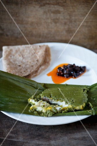 Fish in a herb and chilli marinade wrapped in a banana leaf with chapati and pickles