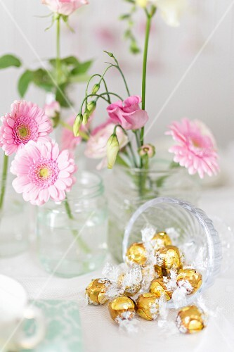 Golden bonbons and pink flowers on a buffet