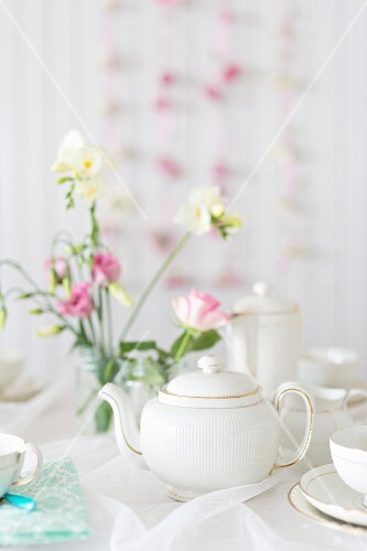 Tea crockery and flowers on a romantic buffet