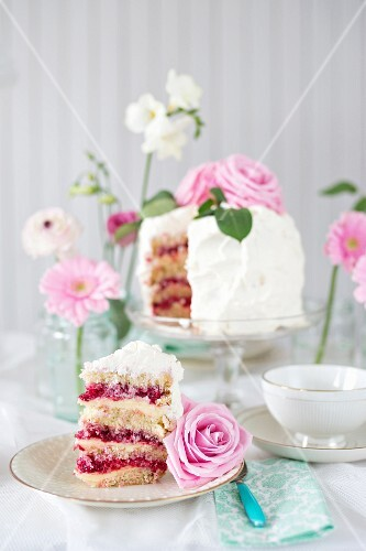 Festive raspberry cake with buttercream, whipped cream and pink roses
