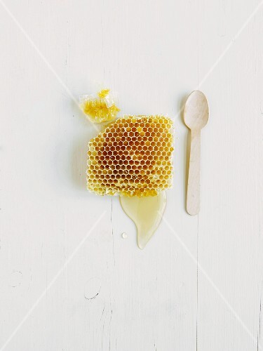 A honeycomb with honey on a white wooden surface (seen from above)