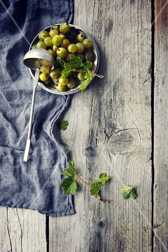 Green gooseberries with leaves in a bowl with a ladle