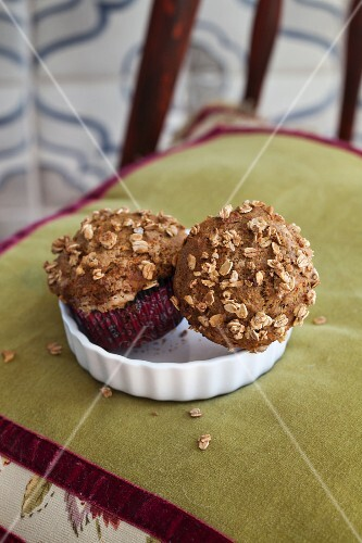 Carrot and lemon muffins with oats on an upholstered chair