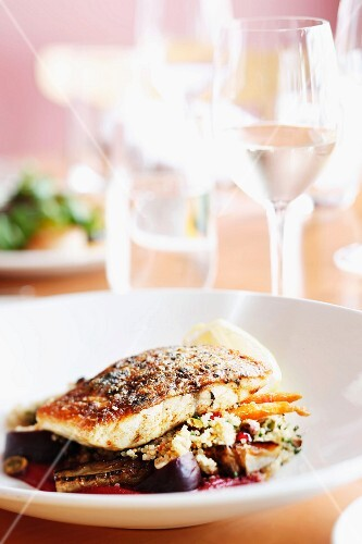 Fried fish on a bed of quinoa and vegetables