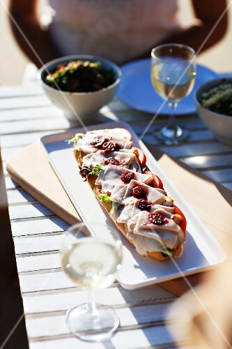 An open ham sandwich with cherry compote outside on a table