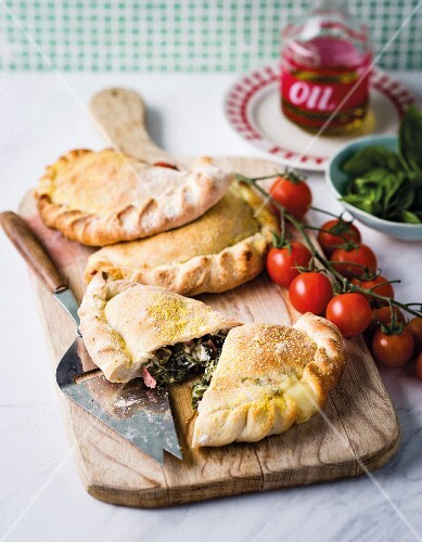 Calzone filled with spinach, salami and mozzarella on a wooden board