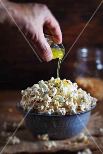 Clarified butter being poured over popcorn