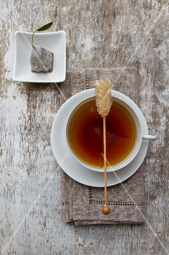 A cup of tea with a stick of rock sugar with a tea bag next to it
