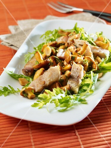 Soused herring with chanterelle mushrooms on a bed of rocket