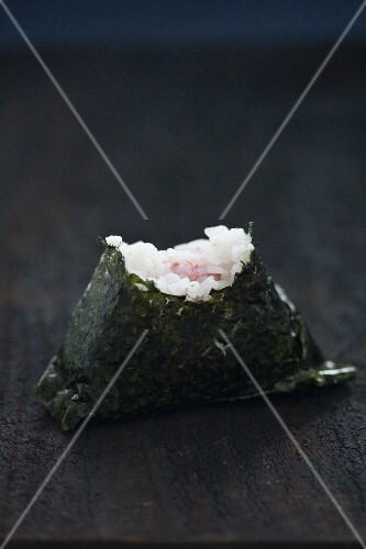 An onigiri sushi with a bite taken out