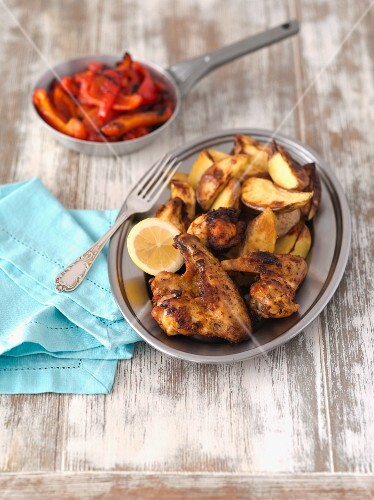 Barbecued chicken wings with baked potatoes and grilled pepper