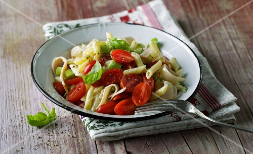 Penne pasta salad with cherry tomatoes, basil and chicken breast