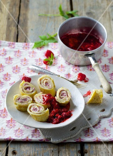 Pancake rolls filled with cream cheese and raspberries served with raspberry compote