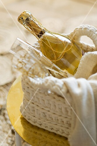 A bottle of champagne with two glasses in a crocheted basket