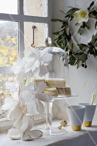 Calissonkonfekt unter einer Glasglocke mit Papierblumengirlande