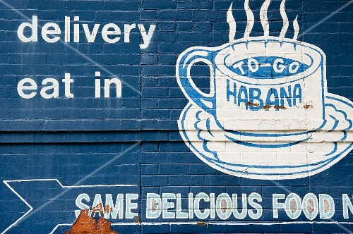 A blue-painted brick wall with a coffee advert in white