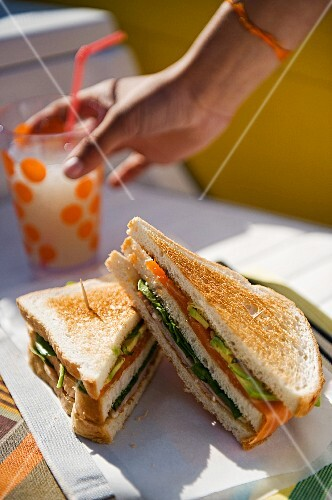 A salmon, lettuce and avocado sandwich served with homemade lemonade