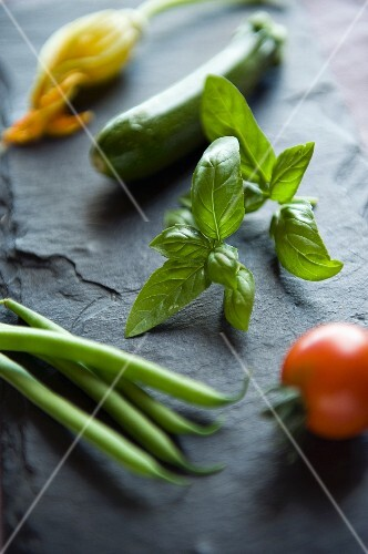 An arrangement of fresh vegetables and basil on a slate surface