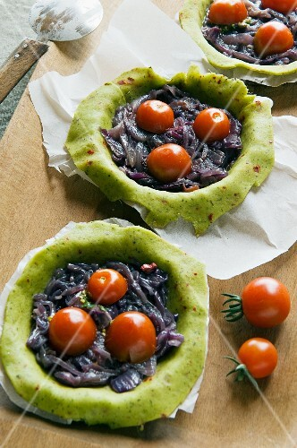 Raw pesto tartlets with onion confit and cherry tomatoes
