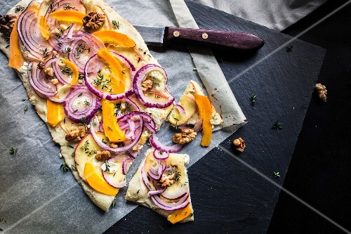 A vegetable pizza with red onions and walnuts