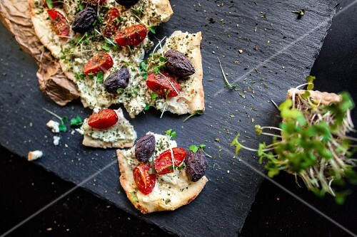 Unleavened bread with tomatoes, olives and fresh cress